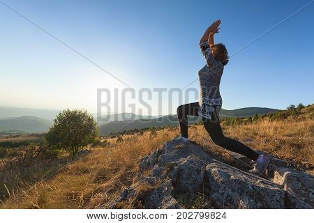 Healthy woman enjoying the beautiful nature rising her arms while stretching toward the setting sun. Lifestyle and fitness concept.