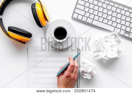 Headphone with white paper note in music studio for dj or musician work on white desk background top view mock-up