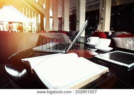 Open laptop computer and cup of coffee lying on a wooden table in hotel bar interior, portable net-book with copy space screen for your information content or text message, distance work via internet