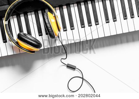 songwriter or dj work place with synthesizer and headphones on white desk background top view mockup