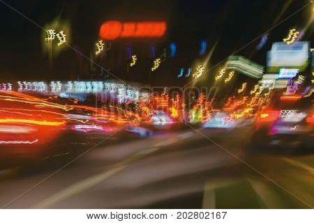 Abstract blurred colorful background of urban street night traffic with bokeh lights. Auto, city street lights and speed. Selective focus.