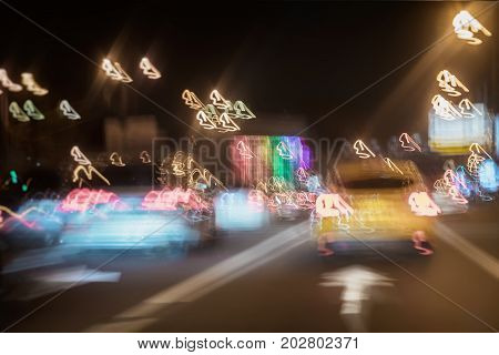Blurred background with yellow taxi, urban street night traffic, lights of cars at dusk on the road of city. Transportation concept. Abstract blur bokeh