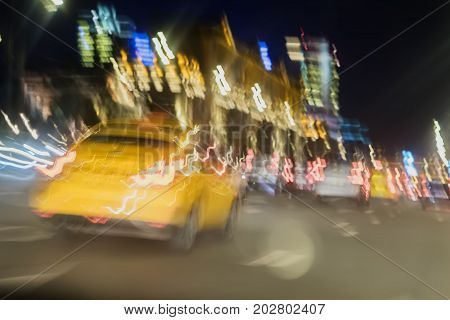 Abstract blurred image of yellow taxi, urban street night traffic with bokeh lights, night time, for background use
