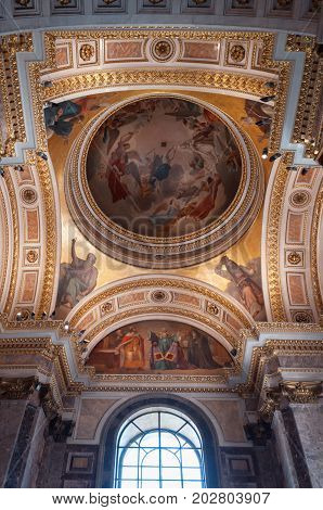 SAINT PETERSBURG RUSSIA - AUGUST 15 2017. Dome ceiling with sculptures and Bible paintings in the interior of the St Isaac Cathedral in Saint Petersburg Russia. Saint Petersburg Russia landmark