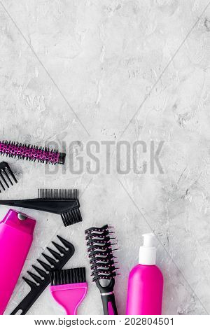 beauty salon pink work tools with comb for hair dress and coloring on stone desk background top view mock up