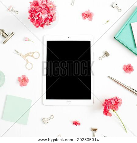 Flat lay fashion office desk. Female workspace with blank screen tablet red flowers accessories mint diary on white background. Top view feminine background.