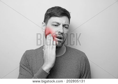Young man suffering from toothache on grey background