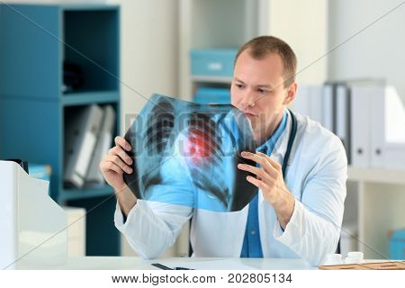 Doctor with x-ray image at table in hospital. Lung cancer concept