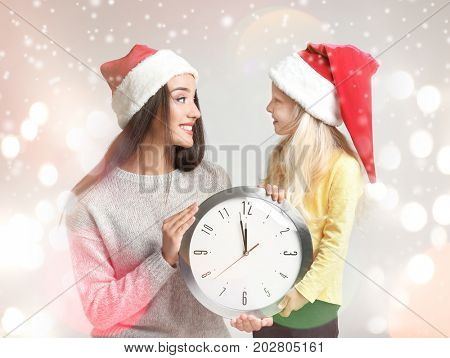 Young woman and cute girl in Santa hats with clock on blurred lights background. Christmas countdown concept