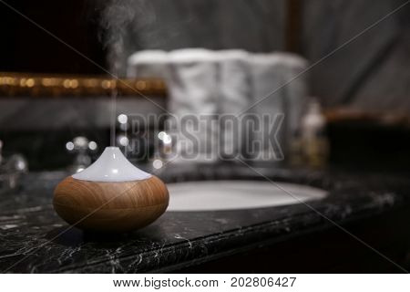 Aroma oil diffuser near marble sink in bathroom