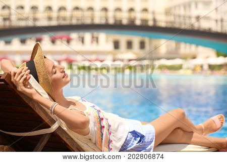 Beautiful young woman relaxing on sun lounger at resort