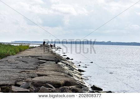 A rocky beach shoreline during a cloudy day.