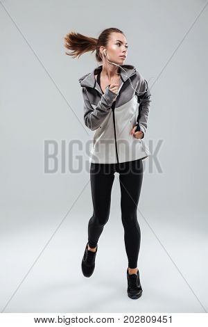 Full length picture of a attractive female runner running in studio and looking away over gray background