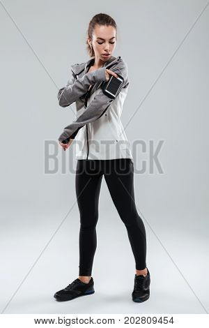 Full length image of a sports woman using smartphone on armband over gray background