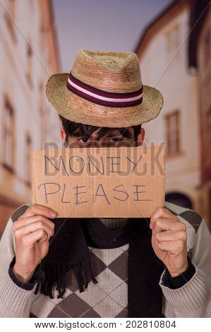 Close up of a homeless with cardboard description of money please, wearing a hat, in a blurred background.