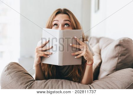 Photo of young pretty lady sitting on sofa indoors. Looking aside covering face with book.