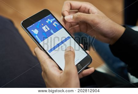 Bangkok Thailand - September 5, 2017 : hand is pressing the Facebook screen on apple iphone6 Social media are using for information sharing and networking.