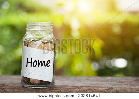 Home Word With Coin In Glass Jar.