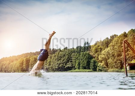 Young man diving into a lake. Careless and risky water jump. Summer vacation dangerous outdoor activity. Side view.