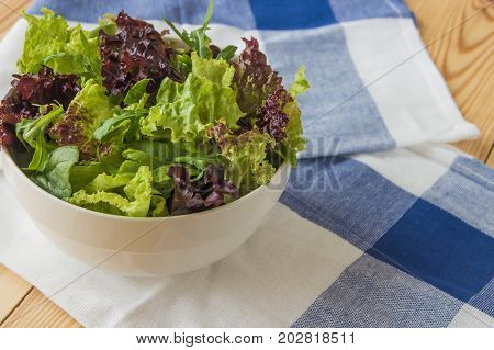 Salad Leaves, Purple Lettuce, Spinach, Arugula. Mixed Fresh Salad In A White Bowl