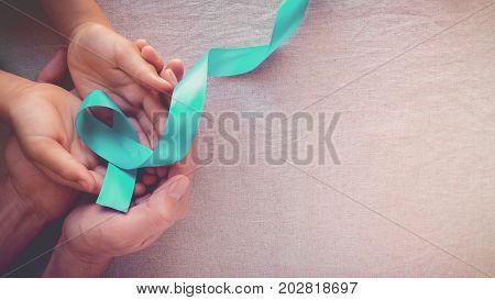 Adult and child hands holding Teal Ribbon toning panoramic banner background Ovarian Cancer cervical Cancer Kidney Cancer and sexual assault awareness