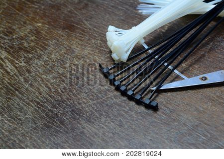 The Cable Tie And  Scissor On Wooden Table