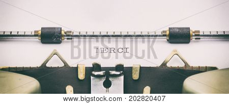 Close-up of of word Merci on a typewriter sheet