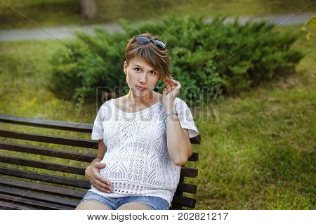 Young attractive pregnant girl sits on a bench in a city park. Respite for a walk outdoors