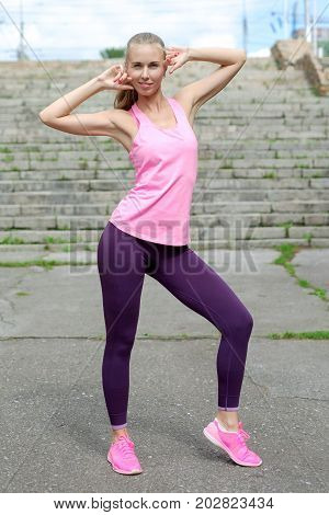 Young woman in sport casual style walk in city park at sunny day after training. Concept of sport lifestyle.