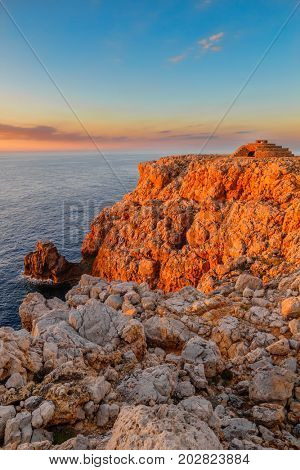 Punta Nati cape in orange sunset light, Menorca island, Spain. One of the most visited point of the island to look at the setting sun.