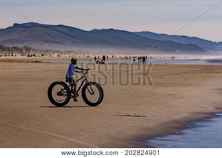Boy riding around on a large fat tire wheeled bike on the beach.