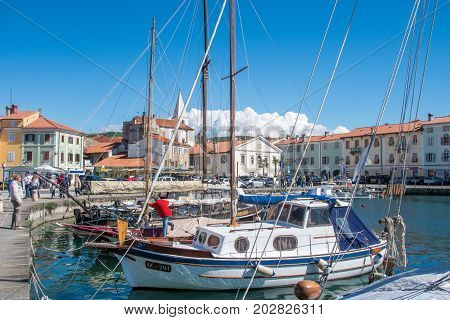 Izola, Slovenia, April 17, 2017: 44MP large panorama of Izola old fishing harbor with traditional fishing boats and old medieval town centre in background