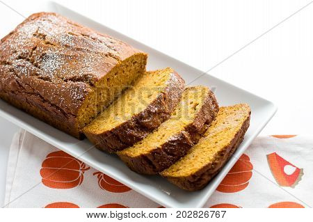 Pumpkin cake loaf slices. Pumpkin bread is a thick sweet cake loaf made with pumpkins. Typically baked in Fall season it is the perfect halloween food as you can use Jack O'Lantern carving leftovers!