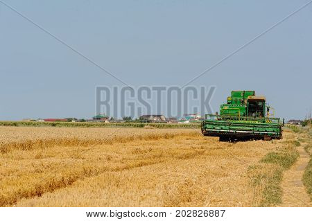 Kuchugury Russia - July 16 2017: Harvester machine to harvest wheat field working. Combine harvester agriculture machine harvesting golden ripe wheat field. Agriculture