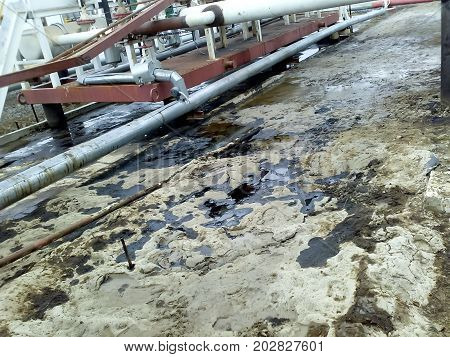 Spilled Oil On Sandy Soil Near Pipelines And Process Equipment. Oil Leaks During Operation And Repai