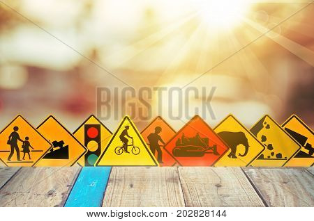 Set Of Traffic Warning Sign On Blur Traffic Road With Colorful Bokeh Light And Old Empty Wood Table