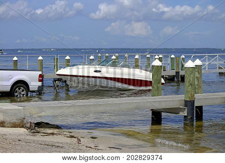 Launching a trailer boat on the boat ramp next to a wooden pier in the Tampa Bay Florida USA