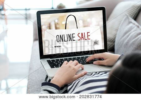 Woman hand typing www. on search bar and online sale over shopping bag on laptop screen background digital marketing business and technology concept