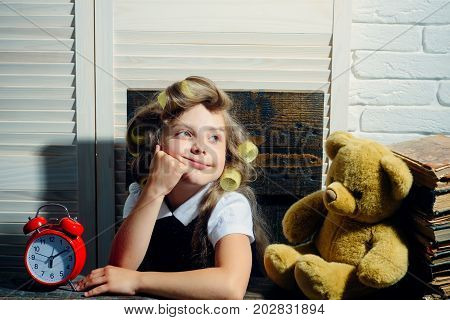 Small girl with curler in hair. Child with bear and alarm clock. Education and childhood. Kid with book. Little baby secretary.