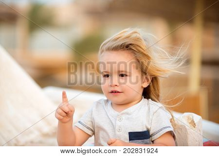 Boy little child with cute smiling face hazel eyes blonde long hair in white shirt pointing with his pointer finger on summer day