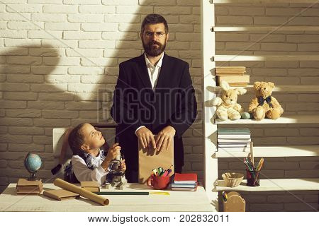Girl and father on white brick background. Family works at desk with school supplies. Back to school and home schooling concept. Schoolgirl and her dad with concentrated faces hold book and microscope