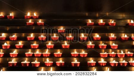 Many burning devotional candles. - Selected Focus narrow depth of field.