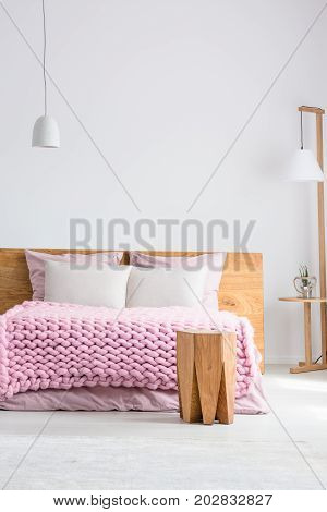 King-size bed with pink overlay and wooden table in white room