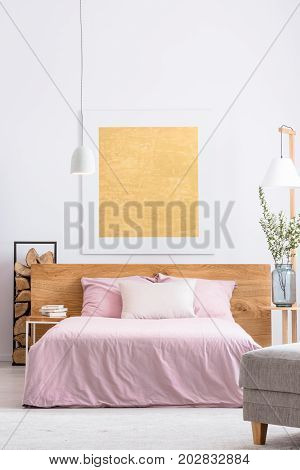 Modern painting is hanging above king-size bed with pink overlay