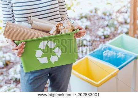 Activist taking care of environment sorting paper waste to proper recycling bin on terrace