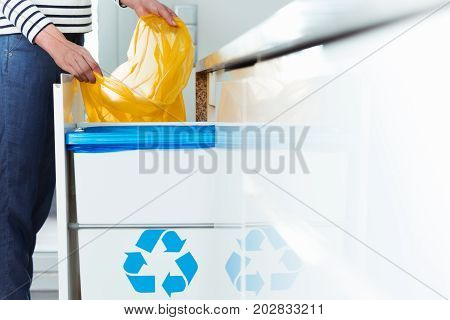 Smart person changing bin bag for recycling waste in eco friendly kitchen with sorting solution