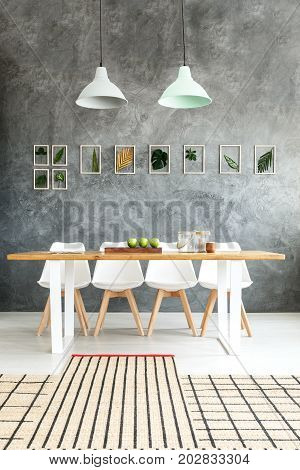 Small rugs with stripes placed on one another in dining room with raw wall