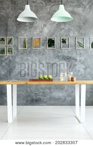 Grey textured wall with leaves in dining room with table and pastel lampshades