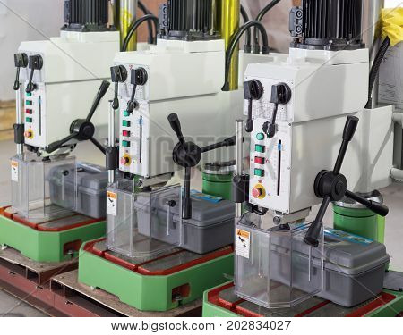Benchtop vertical drilling machines. The machines are arranged in one row. Warehouse of finished products of the machine-building plant.
