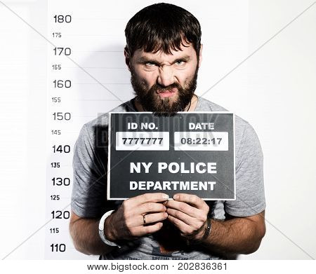 bearded man in handcuffs holds a sign, Criminal Mug Shots.